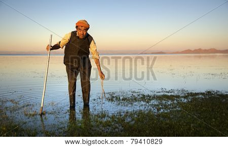 Mongolian man cleaning the lake with the cleaning tool.