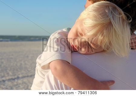 Young Child Sleeping In Father's Arms On Beach