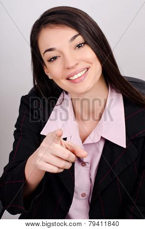 Young smiling business woman pointing finger at viewer.