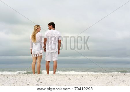 Happy Couple Holding Hands On Ocean Shore On Beach