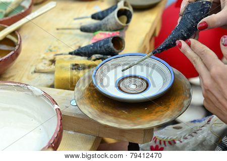 BRASOV, ROMANIA - AUGUST 27, 2014: Woman painting traditional plates at a fair with specific design