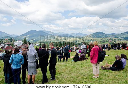 BISTRITA, ROMANIA - SEPTEMBER 8: Gathering of many people on a green lawn watching and listening.