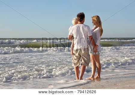 Happy Family Of Three People Playing In Ocean While Walking Along Beach