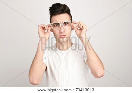 Young man with funny glasses frowning.