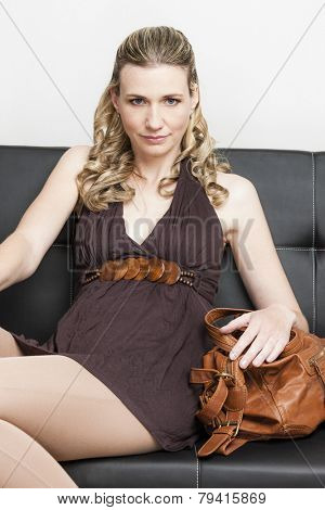 portrait of woman with a handbag sitting on sofa