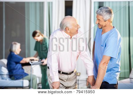 Happy male caretaker looking at disabled senior man at nursing home yard
