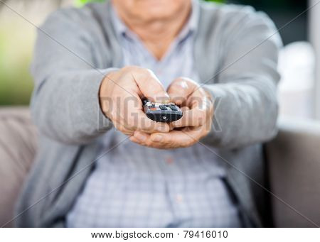 Midsection of senior man using TV remote control while sitting on couch in nursing home