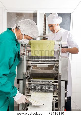 Chefs processing ravioli pasta in machine at commercial kitchen