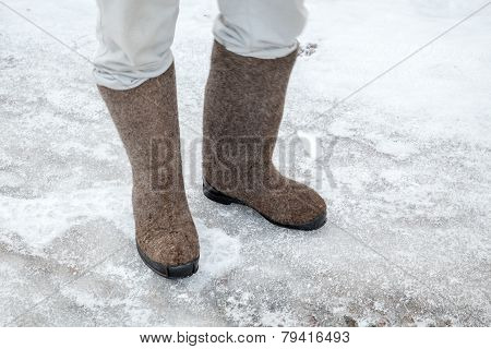 Feet With Traditional Russian Felt Boots On Winter Road