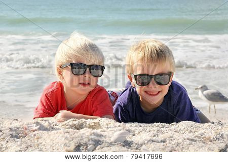 Happy Young Children Laying In The Sun On The Beach