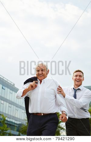 Old and young business man running delayed to an urgent appointment