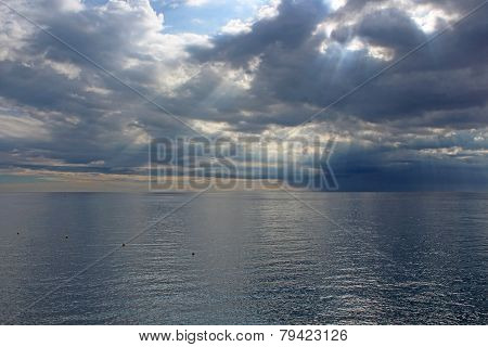 Sun's Rays Passing Through The Storm Clouds Over The Sea