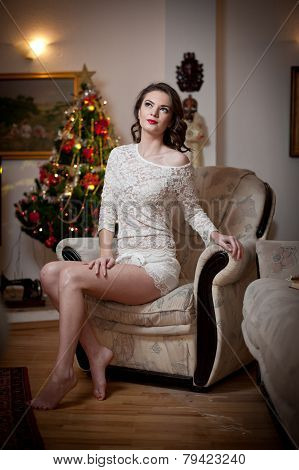 Beautiful sexy woman with Xmas tree in background sitting on elegant chair in cozy scenery. Portrait