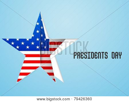 Paper cutout sticky in star shape with United State of American flag for Presidents Day celebration on shiny sky blue background.