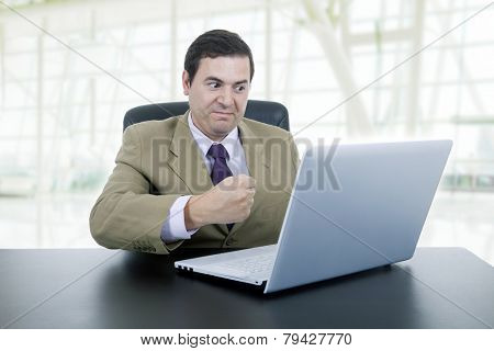 mad businessman working with is laptop, at the office