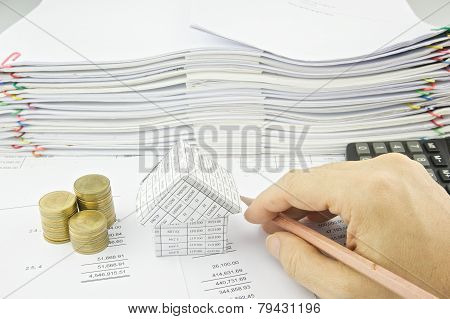 Man Holding Pencil Near House And Gold Coin