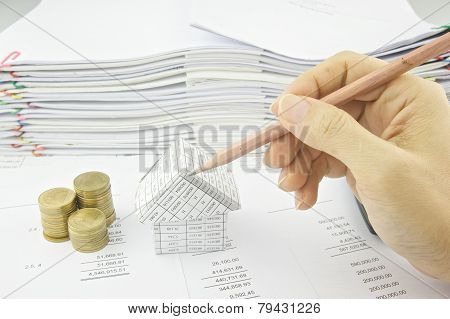 Man Holding Pencil Over House On Balance Sheet