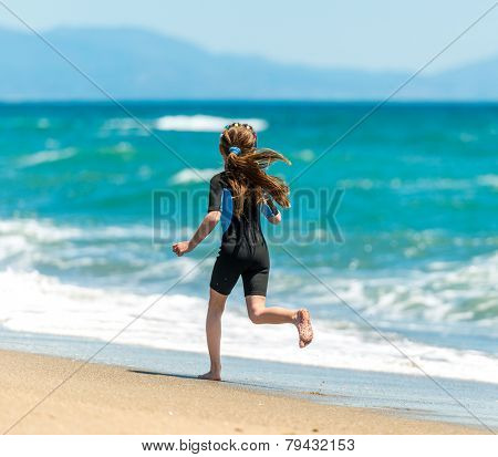 little girl in a wetsuit running along the beach. back view