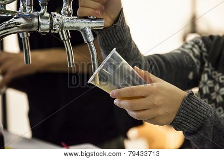 Woman Drawing Beer From Tap