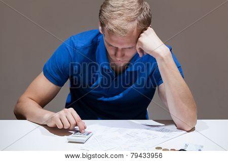 Upset Man Using Calculator
