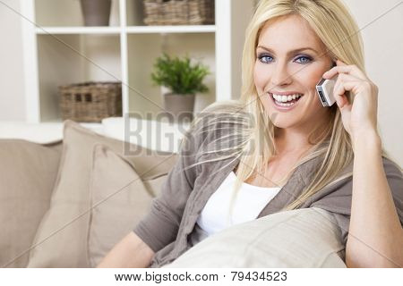 A beautiful young woman talking on her cell phone at home