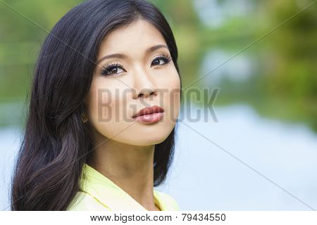 Outdoor portrait of a beautiful young Chinese Asian young woman or girl by a lake with reflections