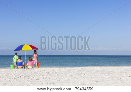 Rear view of a happy family of mother & father, parents daughter & son children sitting in deckchairs under an umbrella on a deserted sunny beach