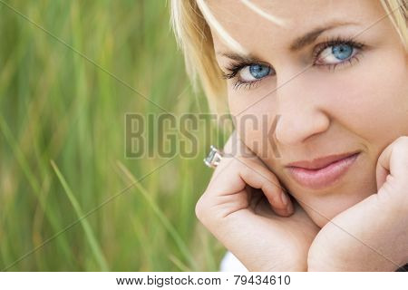 A beautiful blond model with blue eyes against a natural green grass background