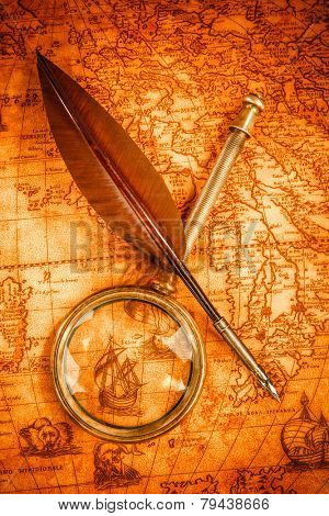 Vintage magnifying glass and quill pen on an old ancient map in 1565. Vintage still life.