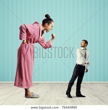 angry woman screaming at small amazed man