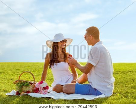 love, dating, people, proposal and holidays concept - smiling young man giving small red gift box with wedding ring to his girlfriend on picnic over blue sky and grass background
