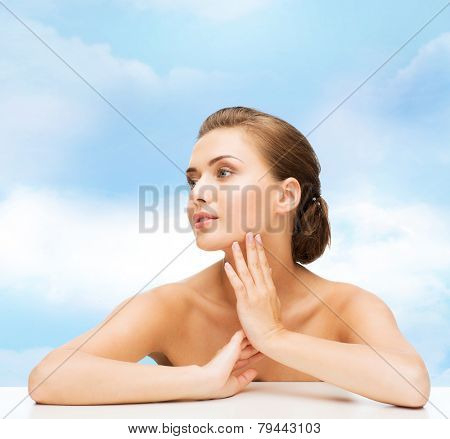 beauty, health and people concept - smiling beautiful woman with clean perfect skin over blue cloudy sky background
