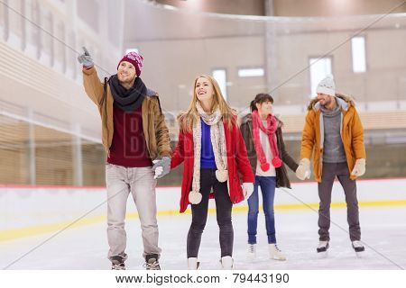 people, friendship, sport, gesture and leisure concept - happy friends pointing finger on skating rink
