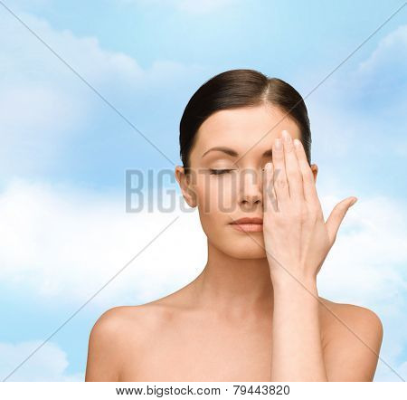 beauty, people and health concept - smiling young woman covering half of face with hand over blue sky background