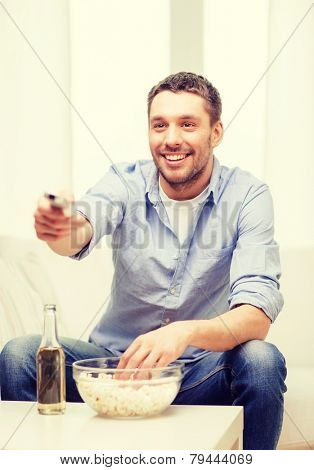 home, technology and entretainment concept - smiling man with beer, popcorn and tv remote control at home
