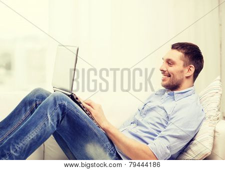 technology, home and lifestyle concept - smiling man working with laptop at home