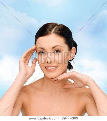 beauty, people and health concept - smiling young woman with bare shoulders over blue sky background