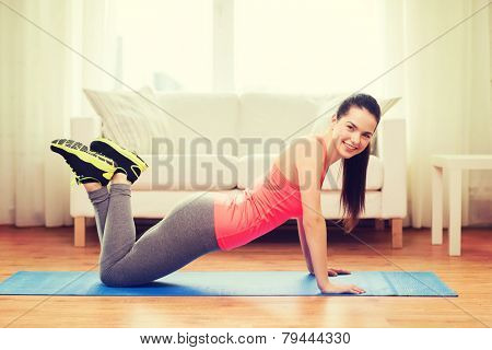 fitness, home and diet concept - smiling teenage girl doing push-ups at home