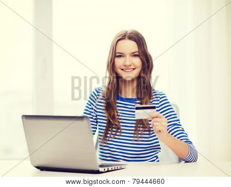 home, technology, banking, money and internet concept - smiling teenage girl with laptop computer and cradit card at home