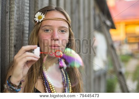 Hippie beautiful girl blows bubbles.