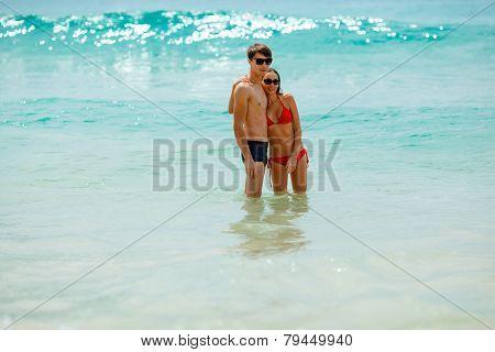 happy couple wearing sunglasses in seawater