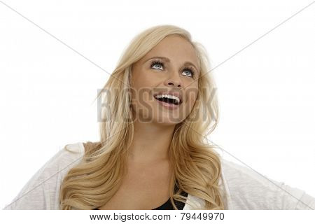 Portrait of beautiful young blonde woman looking up, daydreaming.