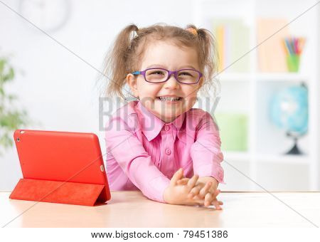 kid with tablet PC in glasses as early education concept
