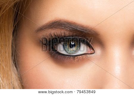 Closeup image of beautiful woman eye with fashion bright makeup