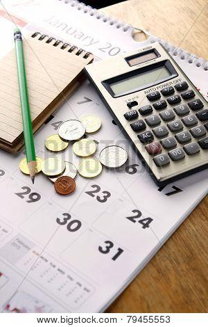 Notebook, calculator, calendar, pencil and coins