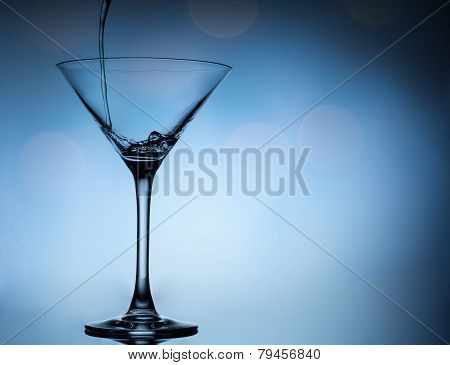 cocktail pouring in martini glasses