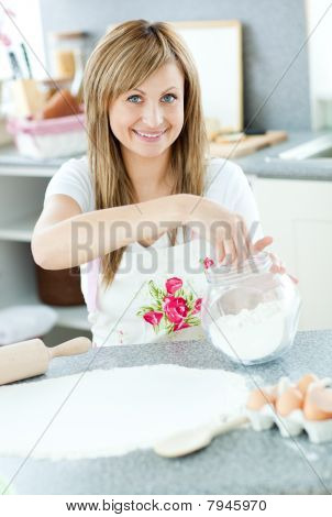 Portrait Of A Cheerful Woman Preparing A Cake In The Kitchen