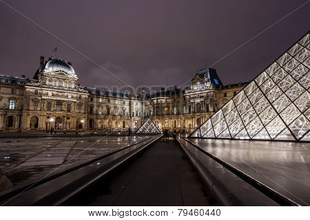 PARIS - JANUARY 4: Louvre Museum and Pyramid at night on January 4 2013. The Louvre is one of the wo
