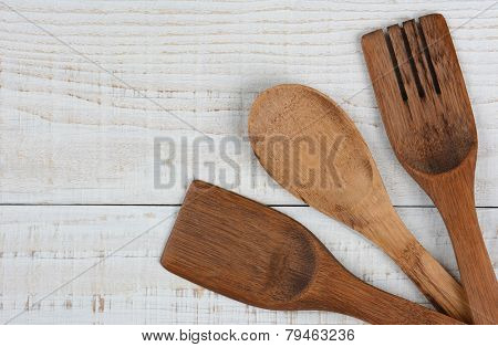 High angle shot of three wooden kitchen utensils in the lower right corner of the frame. The spoon, fork, and spatula have their handles crossed and run out of the image leaving copy space.