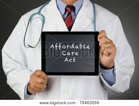 Closeup of a doctor holding a tablet computer with a chalkboard screen with the words Affordable Care Act (Obamacare). Man is unrecognizable.